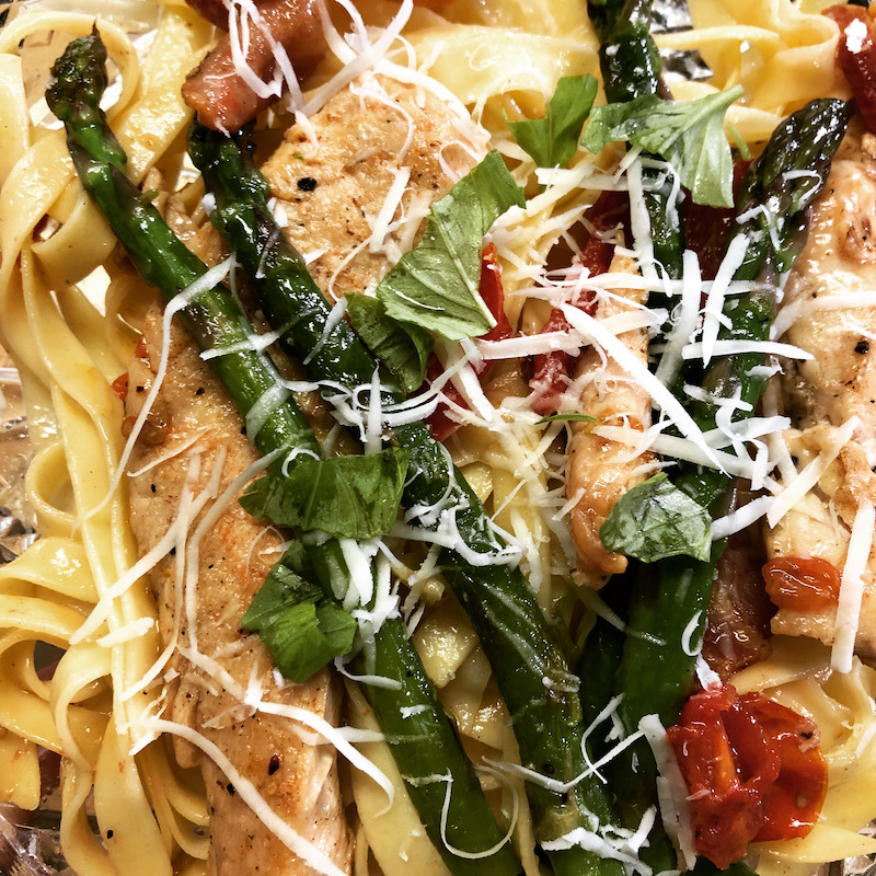 Chicken, bacon, and asparagus over pasta topped with cheese